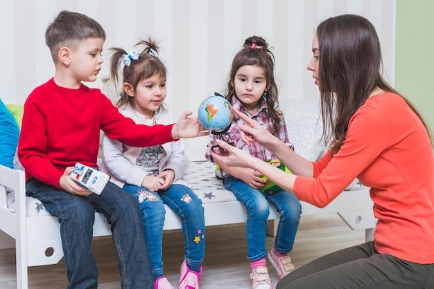 Dzieci Uczy Się Kulę Ziemską Z Kobietą W Sypialni Darmowe Zdjęcia