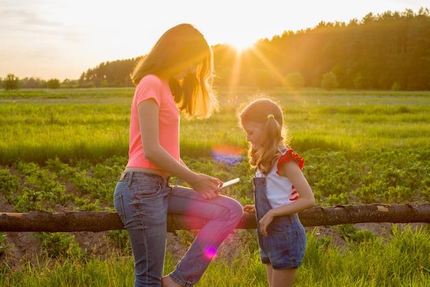 Dzieci w naturze bawią się smartfonem. Premium Zdjęcia