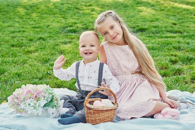 Dzieci w parku na wielkanocnym pikniku z jajkami i królikiem Premium Zdjęcia