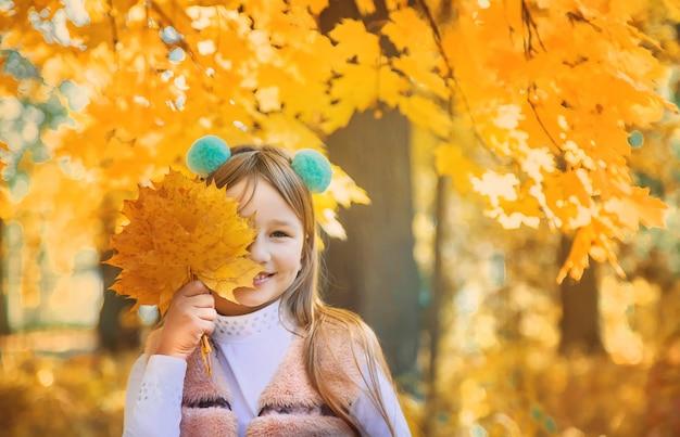 Dzieci w parku z jesiennych liści. selektywne ustawianie ostrości. Premium Zdjęcia