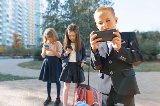 Dzieci w wieku elementarnym ze smartfonami Premium Zdjęcia