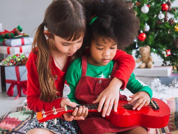 Dzieci wesoło grają na gitarze w boże narodzenie z choinką Premium Zdjęcia