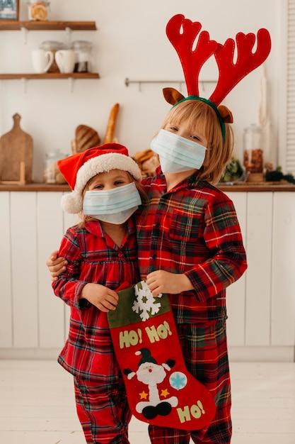 Dzieci Z Maską Medyczną Trzyma Skarpetę świąteczną Premium Zdjęcia