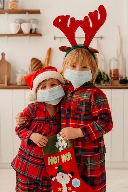 Dzieci Z Maską Medyczną Trzymające Skarpetę świąteczną Darmowe Zdjęcia