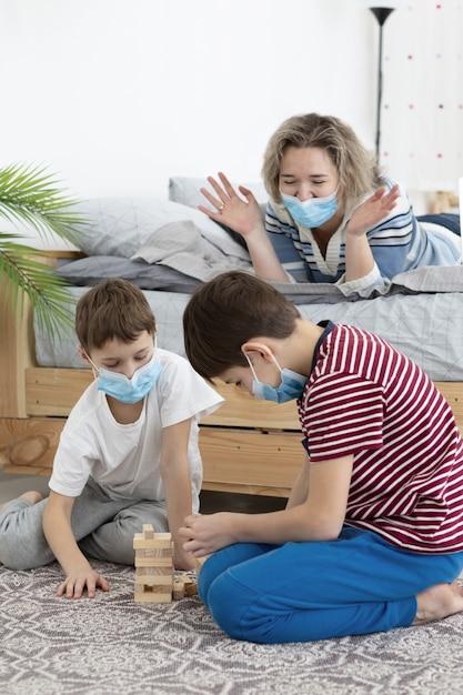 Dzieci Z Maskami Medycznymi Bawiące Się Jengą W Domu Z Matką Darmowe Zdjęcia