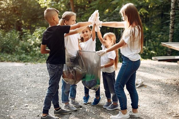 Dzieci zbierają śmieci w workach na śmieci w parku Darmowe Zdjęcia