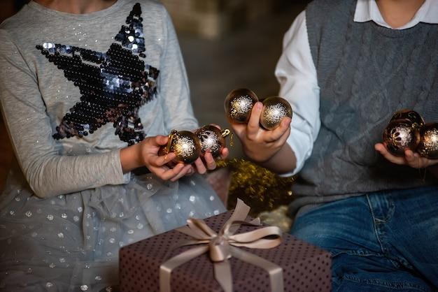 Dzieci Ze Złotymi Kulkami I Prezentami. Premium Zdjęcia