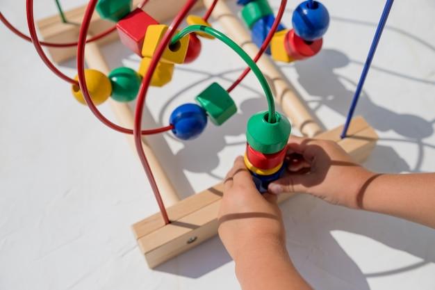 Dzieciak Bawi Się Edukacyjną Zabawką W Domu. Małe Dziecko Grające W Rozwijające Się Gry Dla Dzieci. Szczęśliwe Dziecko Grając Kolorowe Zabawki. Zabawka Edukacyjna. Opracowywanie Gier. Drewniane Przyjazne Dla środowiska Premium Zdjęcia