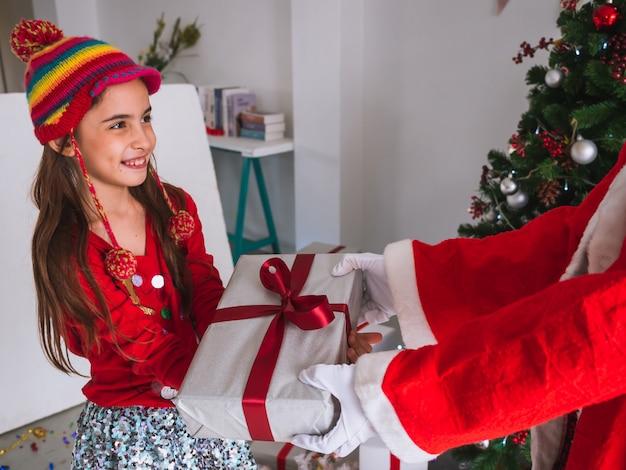 Dzieciak chętnie otrzymuje prezenty od świętego mikołaja Premium Zdjęcia