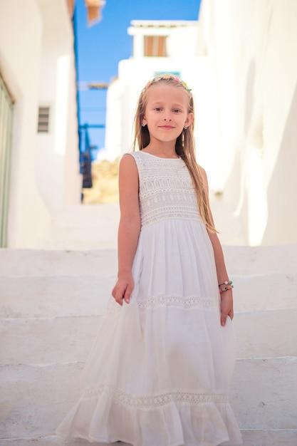Dzieciak na ulicy typowej greckiej tradycyjnej wioski z białymi ścianami i kolorowymi drzwiami na wyspie mykonos Premium Zdjęcia