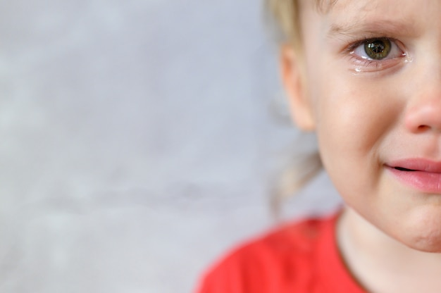 Dzieciak Płacze. Twarz ślicznego, Zmartwionego Czteroletniego Chłopca We łzach. Smutek Dzieci. Szary Tło ścian Betonowych. Miejsce Na Tekst Premium Zdjęcia