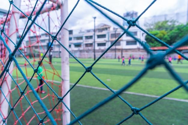 Dzieciak Trenuje Piłkę Nożną W Rozmycie Tła Za Siatką Premium Zdjęcia