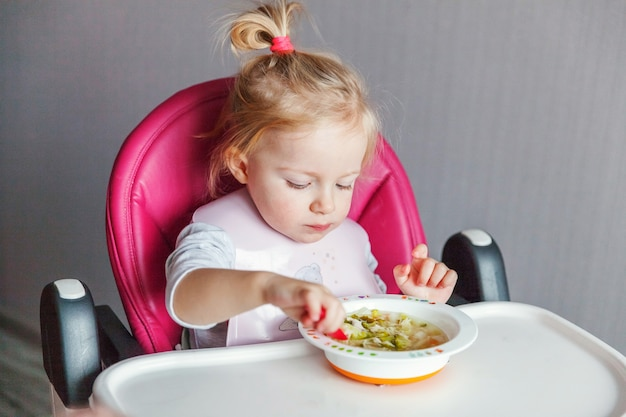 Dziecięca Dziewczynka Z Brudną Twarzą Jedząca Zupę Z łyżką W Wysokim Krzesełku W Kuchni W Domu Premium Zdjęcia