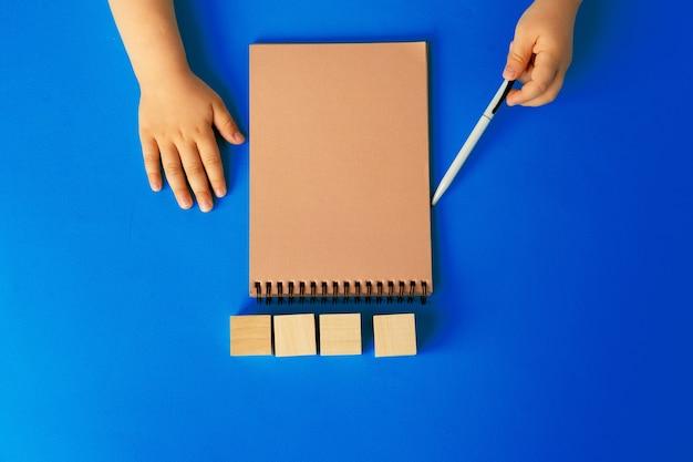Dziecięce Ręce Pisania W Otwartym Notesie, Widok Z Góry, Miejsce Na Kopię Premium Zdjęcia
