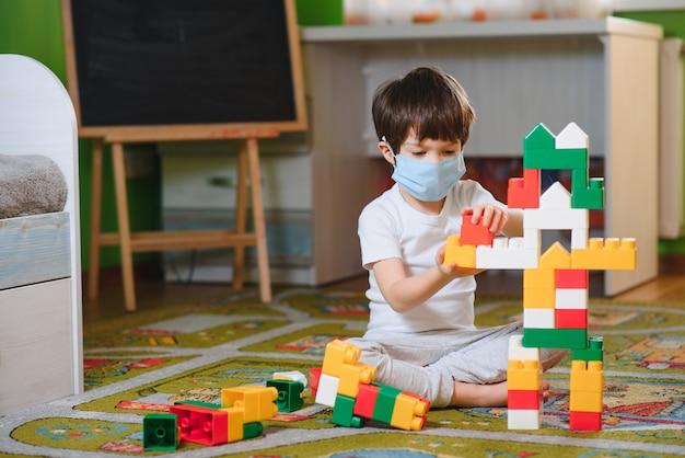 Dziecko Bawi Się Blokami Kolorowe Zabawki. Mały Chłopiec Buduje Wieżę W Domu Lub W Przedszkolu. Zabawki Edukacyjne Dla Małych Dzieci Premium Zdjęcia