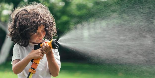 Dziecko Bawi Się Wodą Na Podwórku W Ogrodzie Premium Zdjęcia