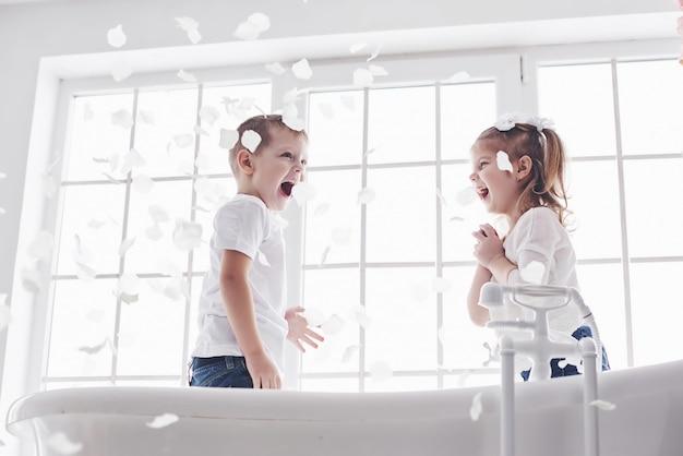 Dziecko Bawi Się Z Płatków Róży W Domowej łazience. Mała Dziewczynka I Chłopiec Fawing Zabawy I Radości Razem. Dzieciństwo I Realizacja Marzeń, Fantazji, Wyobraźni Premium Zdjęcia