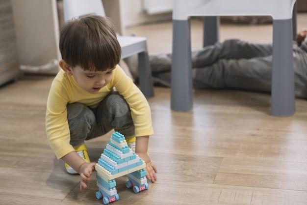 Dziecko Bawi Się Zabawką I Ojcem Niewyraźne Nogi Darmowe Zdjęcia