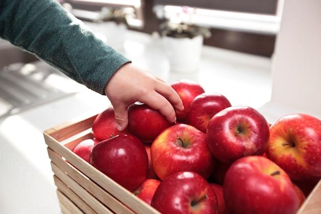 Dziecko Bierze Soczyste Czerwone Jabłko Z Koszyka Premium Zdjęcia