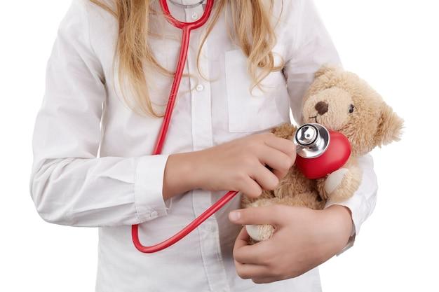 Dziecko Dziewczynka Gra Lekarza Z Pluszową Zabawką Jako żłobek Premium Zdjęcia