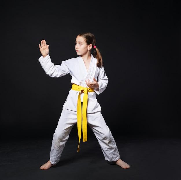 Dziecko Dziewczynka W Karate Garnitur Z Postawy żółty Pasek Pokazuje Premium Zdjęcia