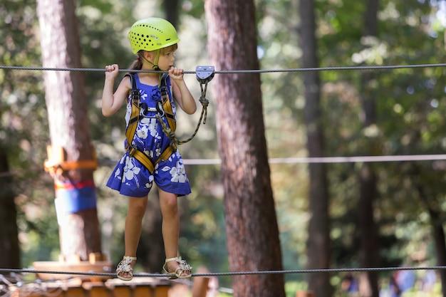 Dziecko dziewczynka w uprząż bezpieczeństwa i kask na sposób liny Premium Zdjęcia