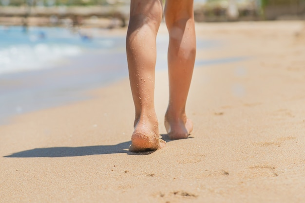 Dziecko Idzie Wzdłuż Plaży Pozostawiając ślady Na Piasku Premium Zdjęcia
