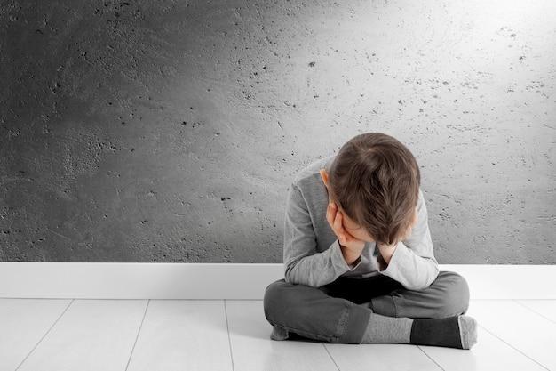 Dziecko, Którego Depresja Siedzi Na Podłodze Premium Zdjęcia