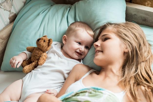 Dziecko Leżące W łóżku Ze Swoją Siostrą Premium Zdjęcia