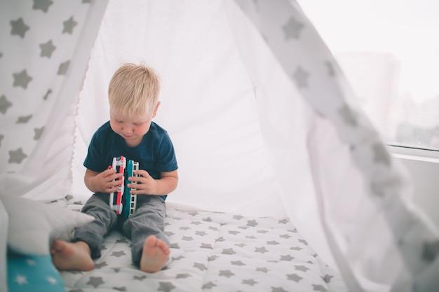 Dziecko Leży Na Podłodze. Chłopiec Bawi Się W Domu Z Samochodzikami W Domu Rano. Nieformalny Styl życia W Sypialni. Premium Zdjęcia