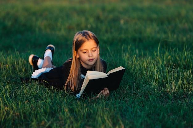 Dziecko Leży Na Trawie I Czyta Książkę W świetle Zachodzącego Słońca. Premium Zdjęcia