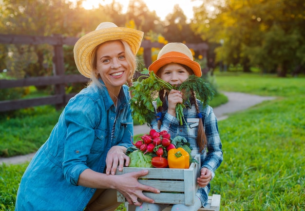 Dziecko Małej Dziewczynki Mienia Mama Kosz świeżych Organicznych Warzyw Z Domowym Ogródem. Premium Zdjęcia