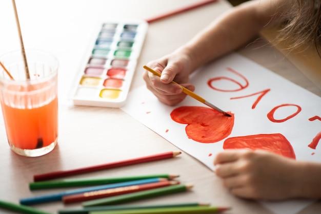 Dziecko Maluje Akwarelami Akwarela Czerwone Serce Na Arkuszu Krajobrazu Na Drewnianym Stole Premium Zdjęcia