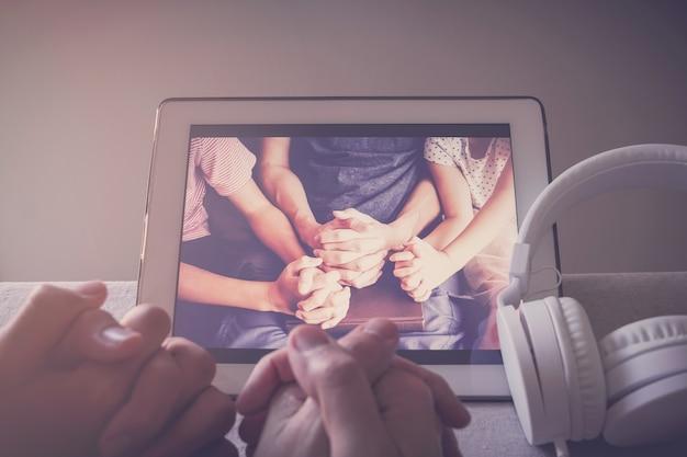 Dziecko Modlące Się Z Rodzicami Za Pomocą Cyfrowego Tabletu, Rodzina I Dzieci Wspólnie Modlą Się Online W Domu Premium Zdjęcia
