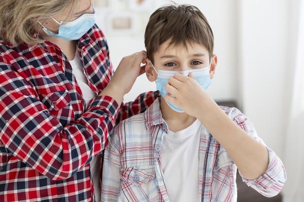 Dziecko Nakłada Maskę Medyczną Z Pomocą Swojej Matki Premium Zdjęcia