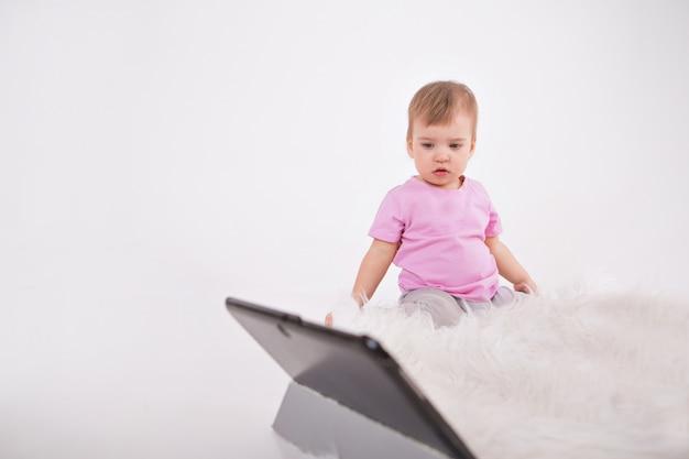 Dziecko Ogląda Bajki Na Tablecie. Szkolenie Domowe Dla Dziewczynki Podczas Kwarantanny Premium Zdjęcia