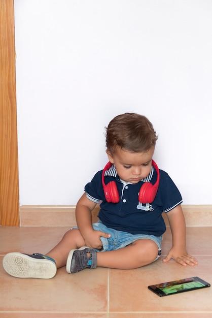 Dziecko Ogląda Filmy Na Telefon Komórkowy Z Czerwonymi Słuchawkami I Granatową Koszulą Premium Zdjęcia