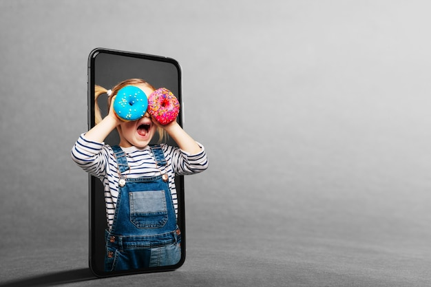Dziecko Patrzy W Lupę Przez Telefon Komórkowy Premium Zdjęcia
