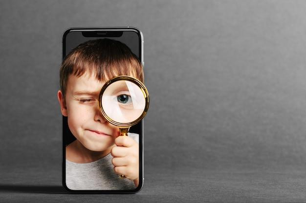 Dziecko Patrzy W Lupę Przez Telefon Premium Zdjęcia