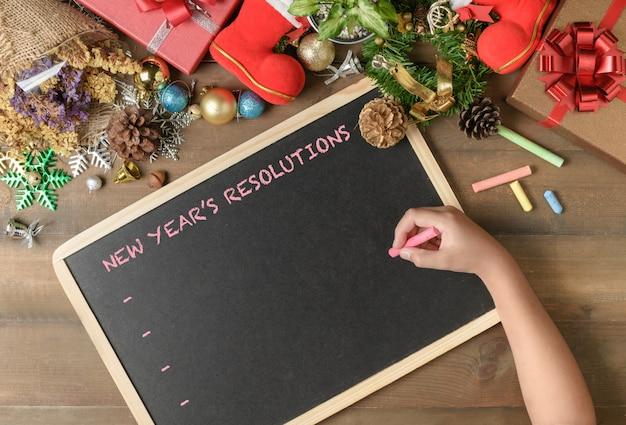 Dziecko pisze noworoczną rezolucję na czarnej tablicy Premium Zdjęcia