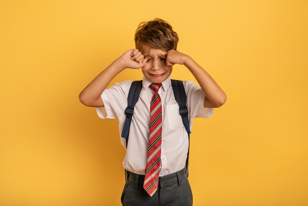Dziecko Płacze, Bo Nie Chce Chodzić Do Szkoły. żółte Tło Premium Zdjęcia