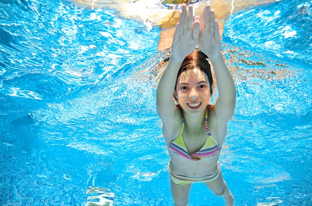 Dziecko Pływa W Basenie Pod Wodą, Szczęśliwa Aktywna Dziewczyna W Goglach Dobrze Się Bawi W Wodzie, Sport Dla Dzieci Na Wakacjach Rodzinnych Premium Zdjęcia