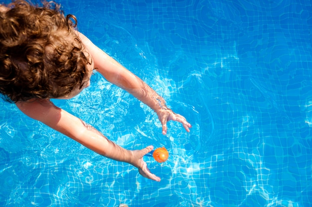 Dziecko Pływa W Basenie, Próbując Dosięgnąć Zabawki W Wodzie, Latem Widok Z Góry. Premium Zdjęcia