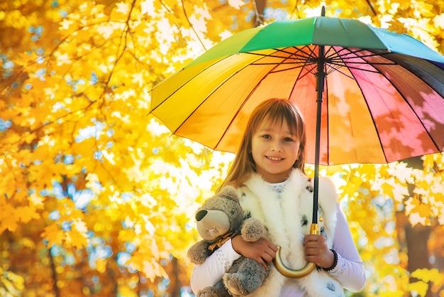 Dziecko pod parasolem w jesień parku. selektywne ustawianie ostrości. Premium Zdjęcia