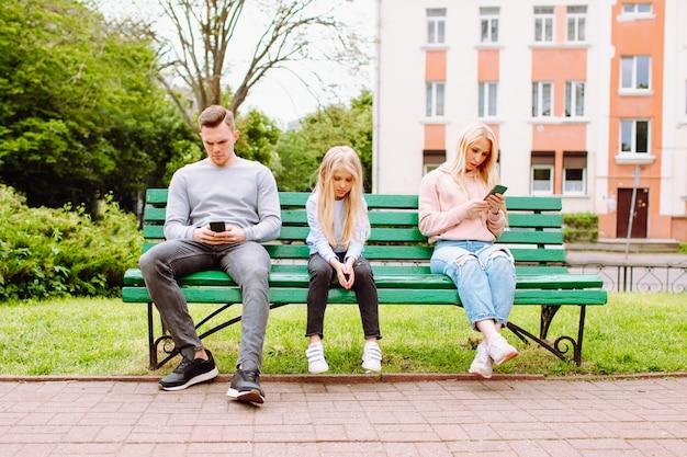 Dziecko Pozostaje Smutne I Bez Opieki, Podczas Gdy Jej Rodzice Gubią Się W Telefonach Komórkowych. Premium Zdjęcia