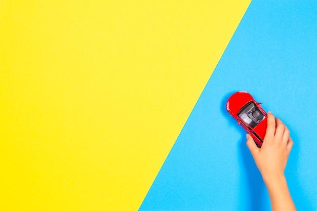 Dziecko Ręka Bawić Się Z Czerwieni Zabawkarskim Samochodem Na Bławym I żółtym Tle Premium Zdjęcia