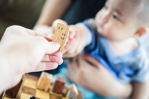 Dziecko Ręki Trzyma Domowego Modela Z Macierzystą Ręką. Premium Zdjęcia