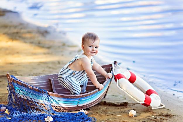 Dziecko Siedzi W łódce Przebrane Za Marynarza Na Piaszczystej Plaży Z Muszelkami Nad Morzem Premium Zdjęcia