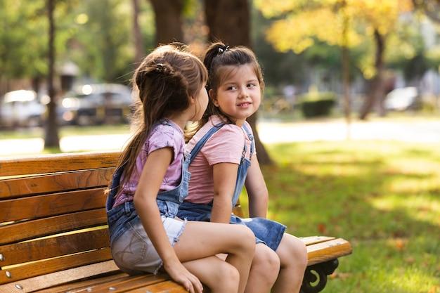 Dziecko siostry siedzi na ławce outdoors Darmowe Zdjęcia