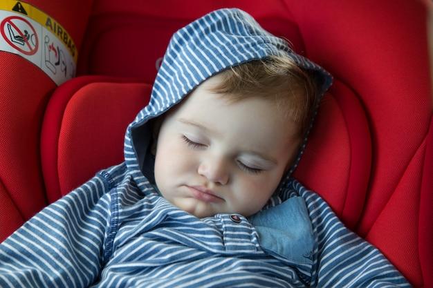 Dziecko śpi W Foteliku Samochodowym Premium Zdjęcia